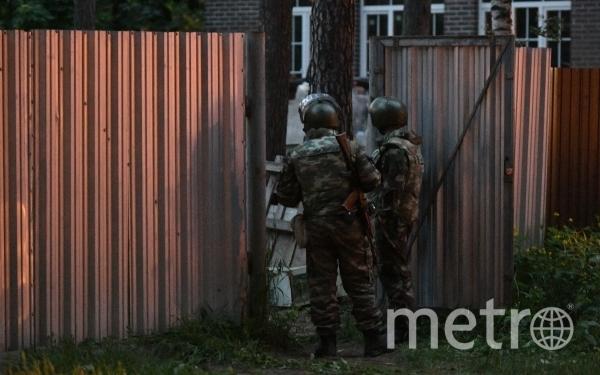 Сотрудники Росгвардии стоят в оцеплении на одной из улиц поселка Кратово, где мужчина забаррикадировался в своем доме и стал стрелять по людям из окна. Фото  Максим Блинов, РИА Новости