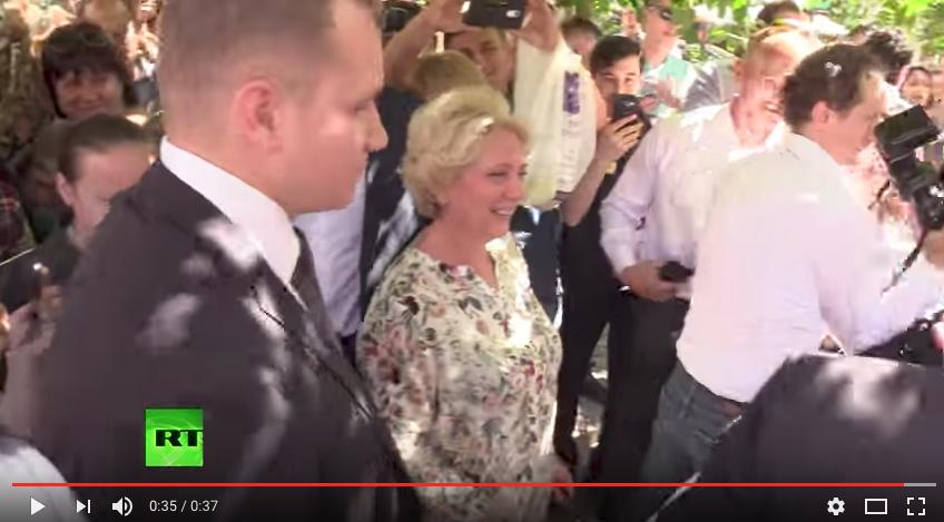 Та самая туристка (справа от охранника). Фото скриншот с канала RT на YouTube
