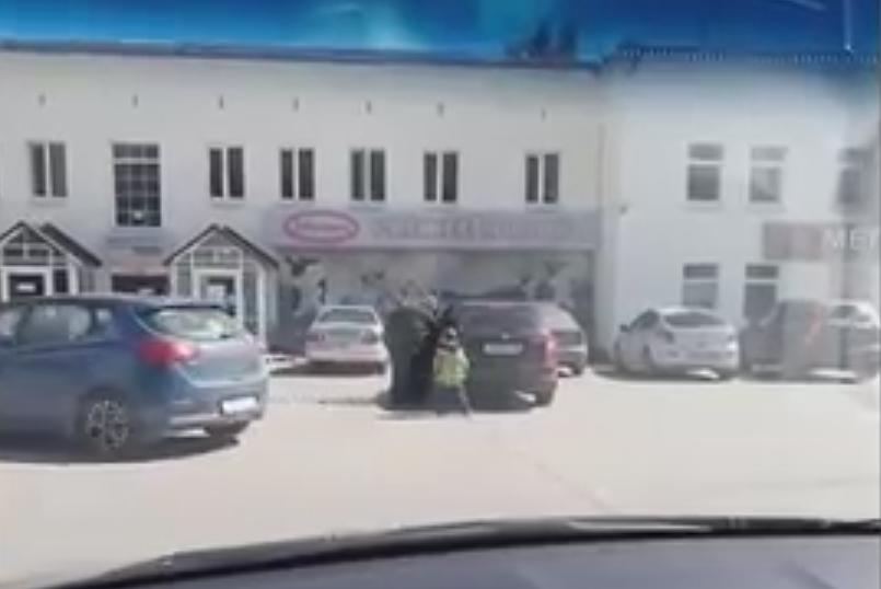 Батюшка усаживает сына в багажник. Фото Скриншот Youtube