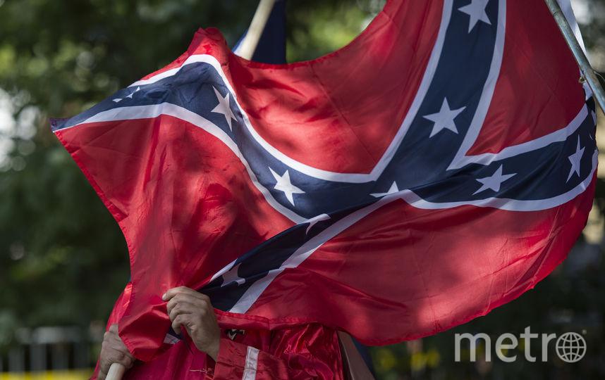 Демонстрант с флагом КША. Фото Getty
