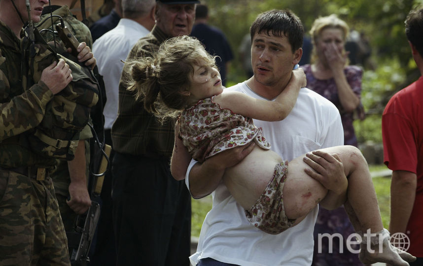 Мужчина выносит потсрадавших из зданий школы. 2004-й год. Фото Getty