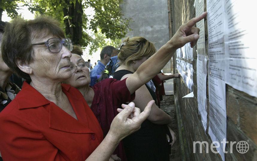 Женщина читает списки погибших, 2004-й год. Фото Getty