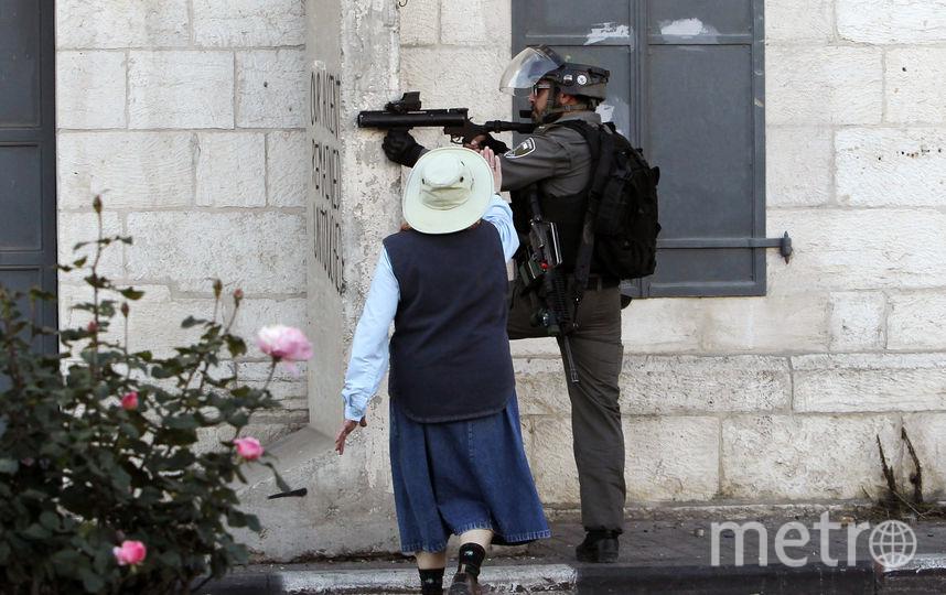 Пожилая женщина бесстрашно разнимает протестующих и силовиков. Фото AFP