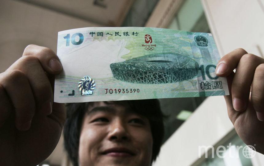 Мужчина с купюрой достоинством десять юаней. Фото Getty