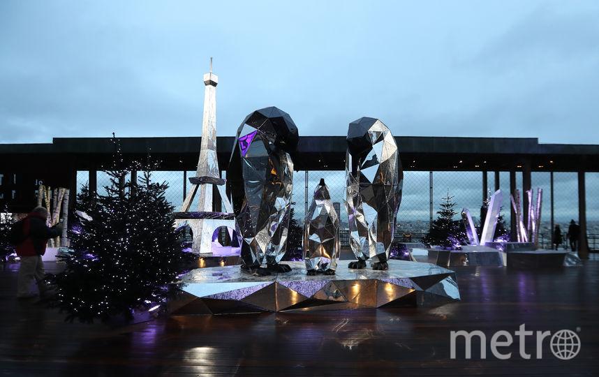 Терраса первого этажа Эйфелевой башни в Париже украшена заснеженными ёлочками, скульптурами пингвинов и многогранными зеркалами. Фото AFP
