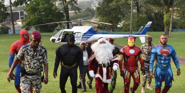 """Бэтмен, Санта-Клаус, Железный Человек и Супермен в президентском дворце в Абиджане (Кот-д'Ивуар) во время детского рождественского мероприятия, организованного Фондом """"Дети Африки""""."""