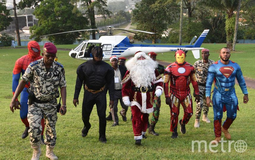 """Бэтмен, Санта-Клаус, Железный Человек и Супермен в президентском дворце в Абиджане (Кот-д'Ивуар) во время детского рождественского мероприятия, организованного Фондом """"Дети Африки"""". Фото AFP"""