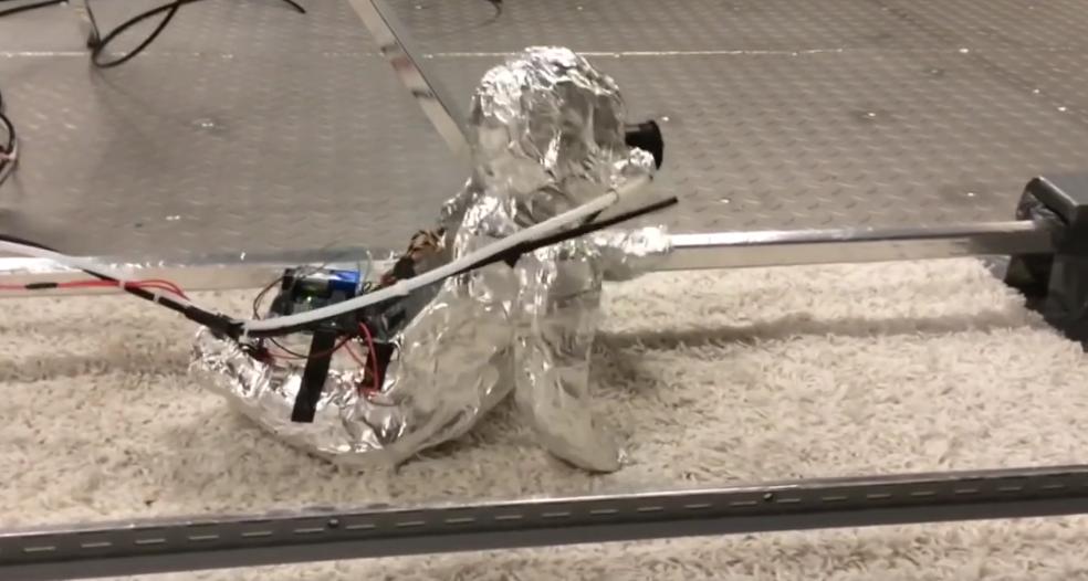 Робот-ребёнок из фольги ползает по полу и дышит пылью. Фото Все - скриншот YouTube