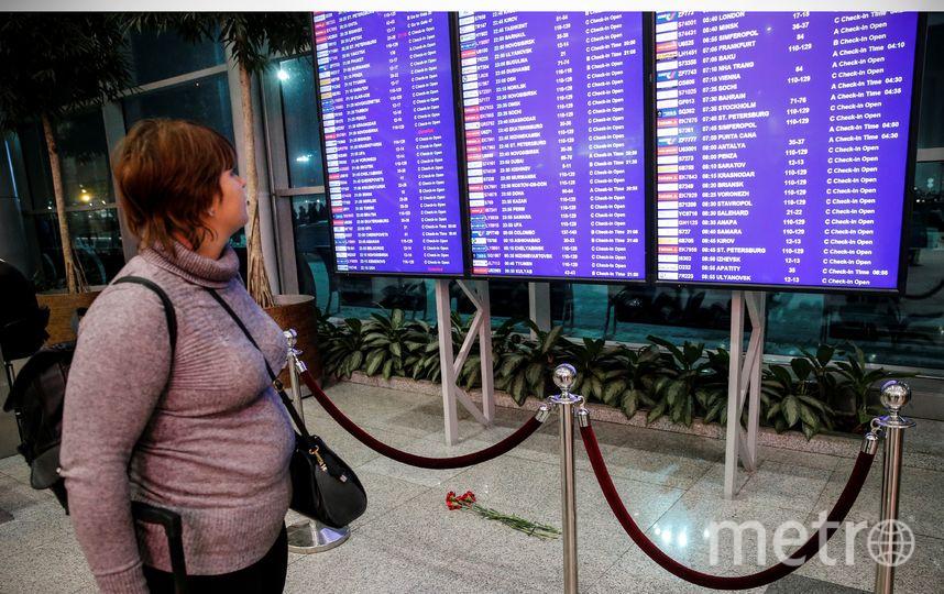 Люди оставляют цветы под расписанием полётов в столичном аэропорту Домодедово. Фото AFP