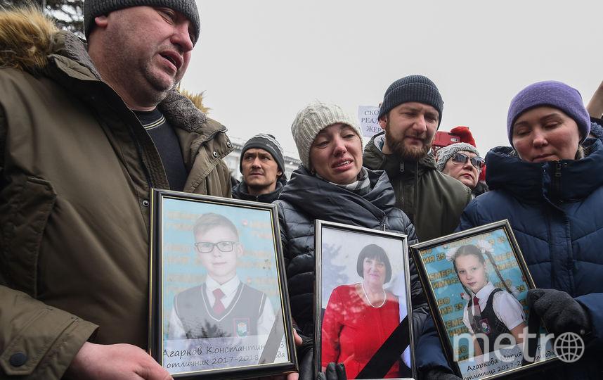 Супруги Агарковы держат в руках фотографии погибших детей и бабушки. Фото AFP