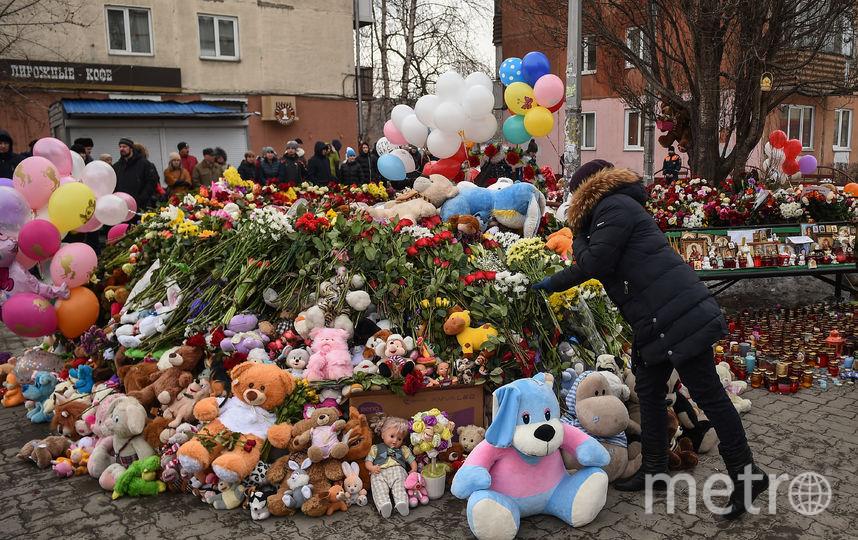 Жители Кемерово несут цветы к месту пожара. Фото AFP