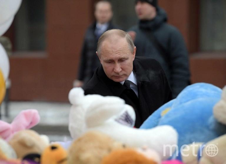 Путин возлагает цветы к стихийному мемориалу погибших во время пожара в Кемерово. Фото AFP