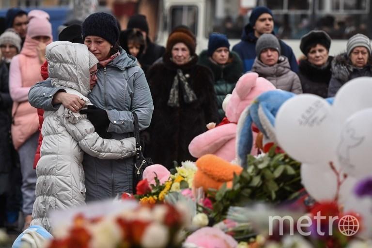 """Люди несут цветы к стихийному мемориалу у фасада ТЦ """"Зимняя вишня"""" в кемерово. Фото AFP"""