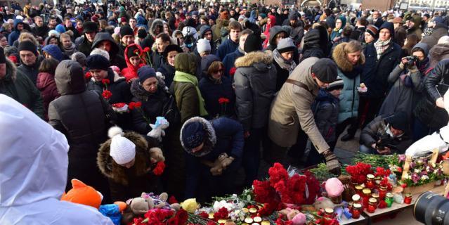Сотни людей приходят к временному мемориалу на Манежной площади в центре Москвы, чтобы почтить память погибших при пожаре в торговом центре Кемерово.