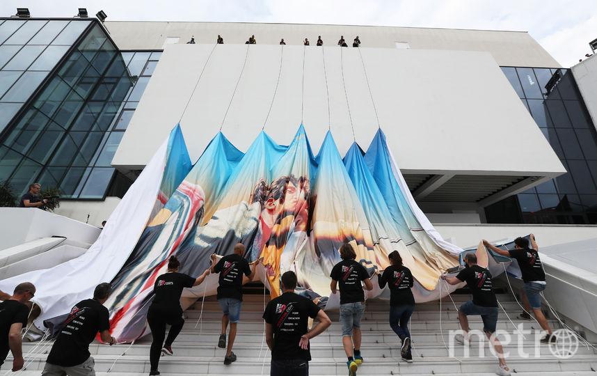 Рабочие растягивают баннер над входом во Дворец фестивалей, на ступенях которого скоро расстелют красную дорожку. Фото AFP