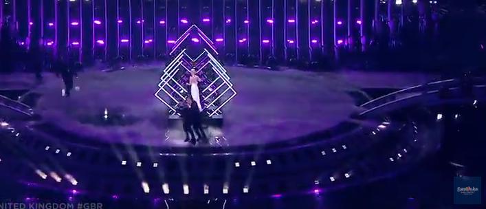 Мужчина вырвался на сцену, с силой отобрал микрофон у SuRie и попытался начать петь. Фото скриншот YouTube