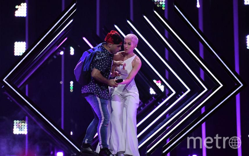 неизвестный мужчина решил добавить эпатажа номеру британской певицы SuRie. Он выбежал из зрительского зала, силой забрал у неё микрофон и попытался начать петь. Фото AFP