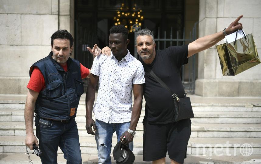 Прохожие фотографируются с Мамуду Гассама. Фото AFP