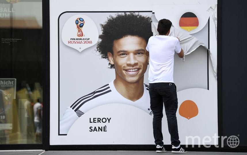 Рабочий снимает портрет Сане с фасада здания Музея немецкого футбольного союза после оглашения заявки сборной на мундиаль. Фото AFP