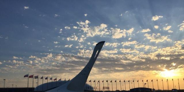 "Олимпийский факел около стадиона ""Фишт"", где проходят матчи чемпионата мира по футболу."