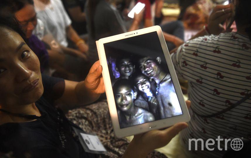 Родственники пропавших детей показывают на планшете их снимки, которые сделали спасатели в пещере. Дети живы. Фото AFP