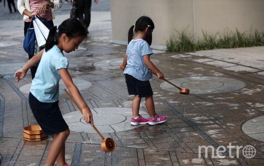 В Токио расплескивают воду, чтобы охладить улицы. Фото AFP