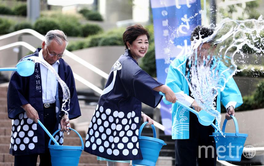 Губернатор Токио расплескивает воду, чтобы охладить улицы. Фото AFP