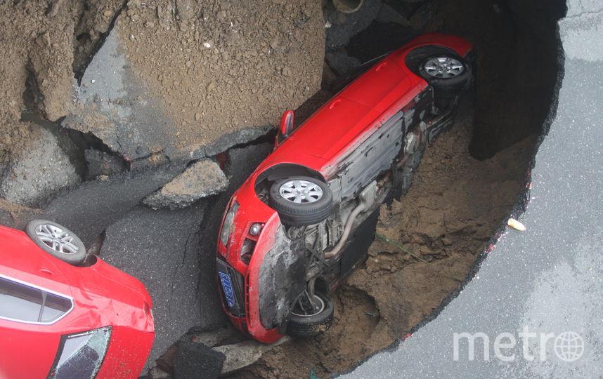 Авто провалились в яму, размытую дождями. Фото Getty