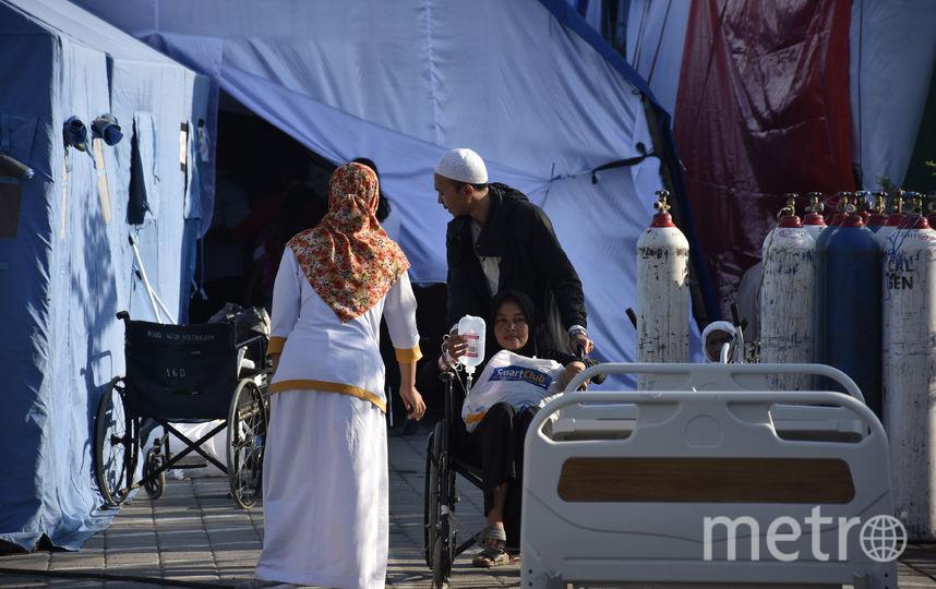 Сильные землетрясения потрясли Индонезию. На фото: муж везёт жену в инвалидном кресле во временный госпиталь, сооружённый в тенте. Фото AFP