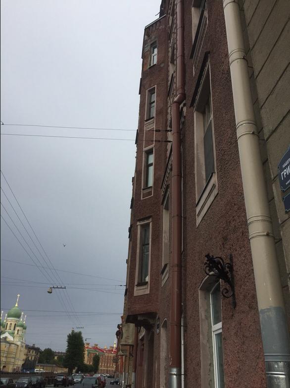 На одной из улиц Петербурга часть фасада здания обрушилась на машину.