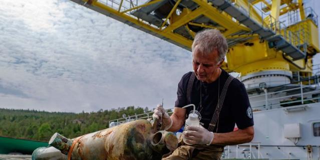 Археолог Роман Прохоров удаляет грязь с бронзовой пушки.