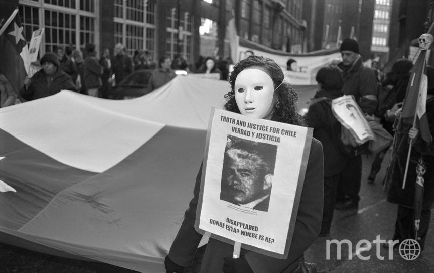 Женщина в маске держит плакат с фото мужчины, похищенного во времена диктатуры Пиночета в Чили. Фото Getty