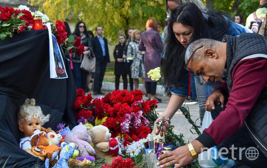 Люди приносят цветы к зданию политехнического колледжа, чтобы отдать дань памяти погибшим. Фото AFP