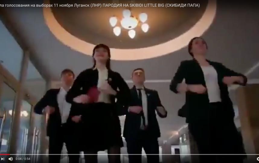 На видео люди в строгих костюмах танцуют и призывают прийти с паспортом на избирательный участок 11 ноября. Фото Скриншот Youtube