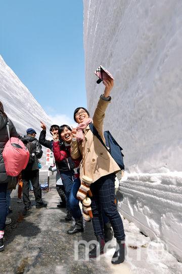 Туристы фотографируются на фоне сугробов в японском городе Тояма. Фото Getty