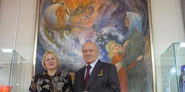 Рита (слева) на фоне картины, на которой изображён тот самый день.