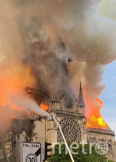 У горящего собора Парижской Богоматери обрушились шпиль, часы и крыша. Фото AFP