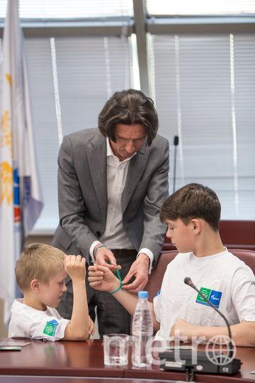 Алексей Смертин вызвался помочь повязать браслеты детям. Фото Предоставлено организаторами