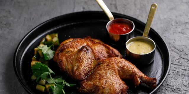 Половинка запеченого цыпленка с фирменным кетчупом и огурцами кимчи в ресторане KETCH UP.