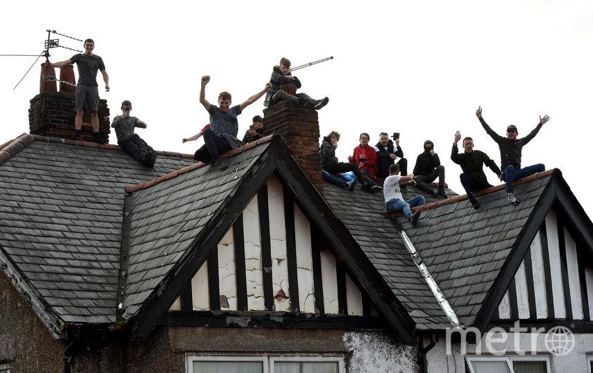 Некоторые болельщики поднялись на светофоры, дорожные знаки и крыши зданий в поисках лучшей точки обзора. Фото AFP