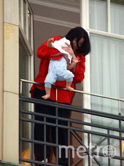 Майкл Джексон держит своего восьмимесячного сына на балконе Adlon в Белине 19 ноября 2002. Фото Getty