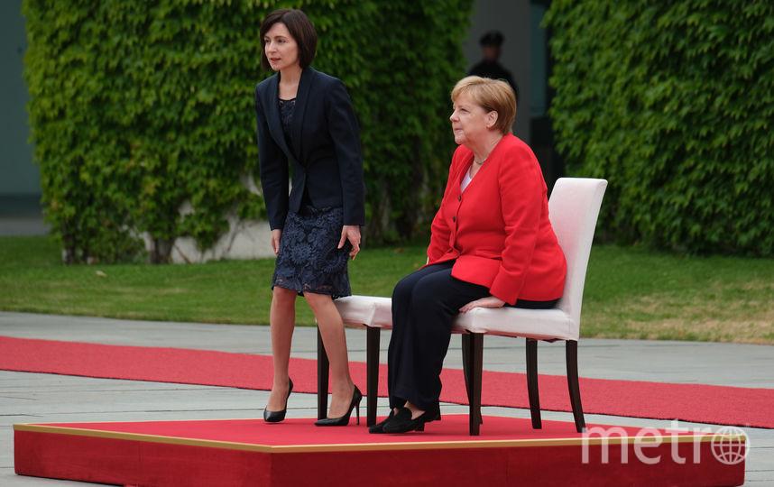 Меркель и премьер-министр Молдавии Майя Санду прослушали гимны двух стран сидя на стульях с белой тканью. Фото Getty
