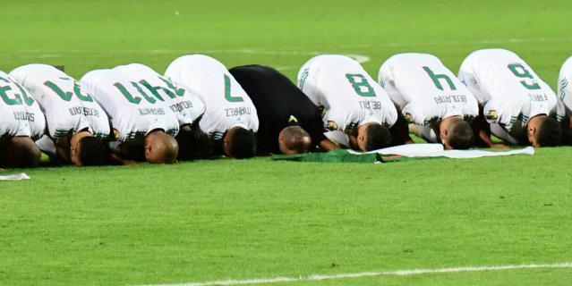Футболисты Алжира молятся перед своими трибунами после победы на Кубке Африки.