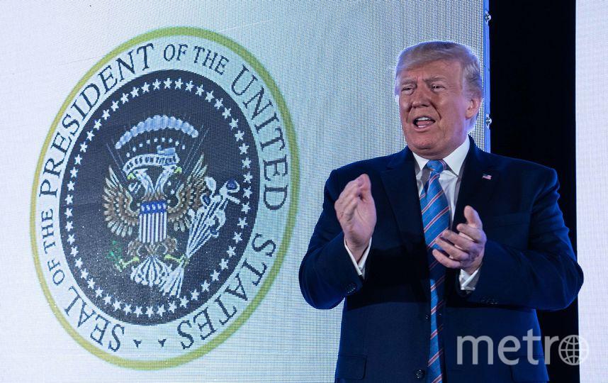 Дональд Трамп на фоне неправильной прездентской печати. Фото AFP