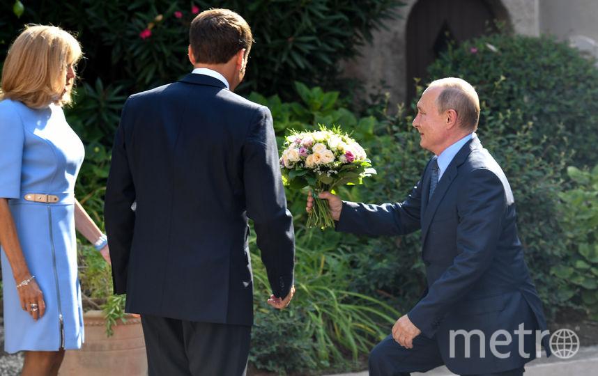 Владимир Путин вручает букет Брижит Макрон. Фото AFP