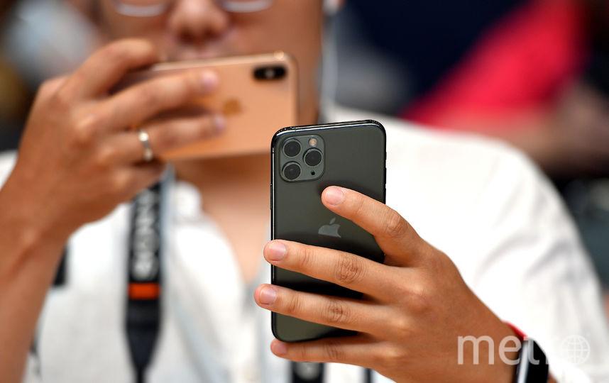 Люди с выставочными смартфонами на презентации. Фото AFP