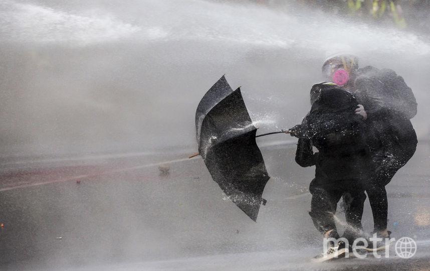 Протестующие использовали зонтики, чтобы защититься от водометов. Фото AFP