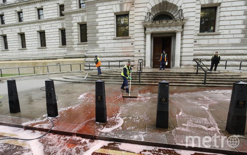 В результате инцидента около 1800 литров красной пищевой краски было вылито у главного входа в здание. Фото AFP