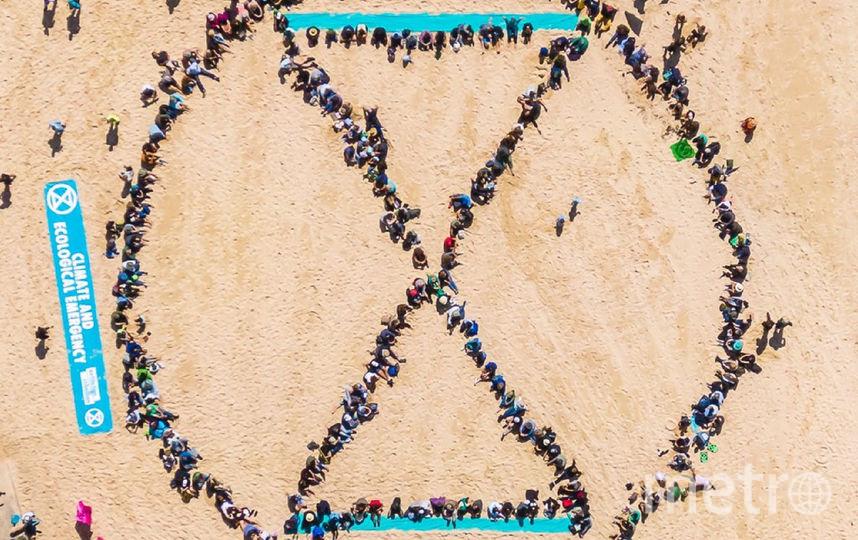 Активисты образовали логотип экологического движения Extinction Rebellion. Фото скриншот @XRebellionAus