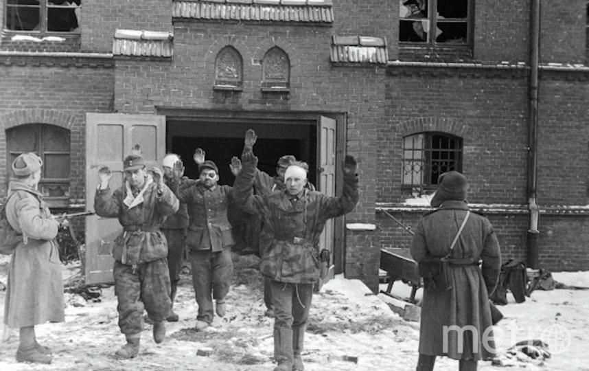 Пленные гитлеровцы выходят из дверей здания под конвоем советских бойцов. Фото РИА Новости